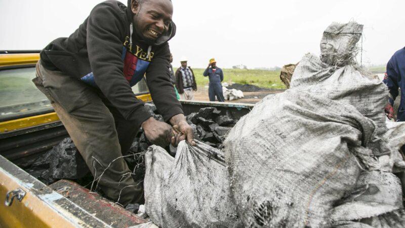 Man loading coal on truck from Emmy-winning episode.